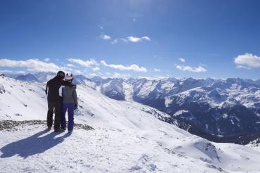 Bergpanorama, Blick ueber die Berge des Zillertals, Blick vom Uebergangsjoch (2500 Meter Hoehe), Paar, Geschwister, Skifahrer, Jugendliche, Kinder, Pause, Gegenlicht, schneebedeckte Berge, Winterferien, Skigebiet, Zillertal Arena, Zillertal, Tirol, Oesterreich