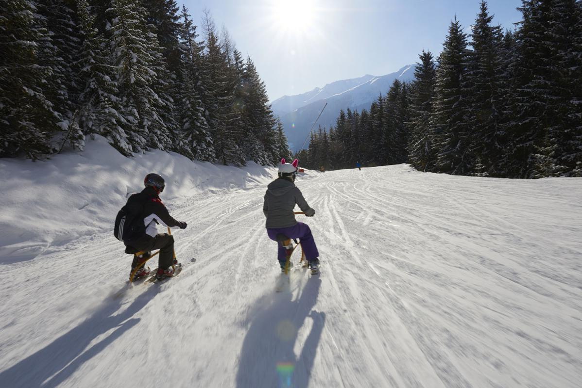 Snowbike, junges Paar, Maedchen und Junge mit Helm auf Snowbike, Piste, Schnee, Berge, verschneite Baeume, bei Rosenalm, Zillertalarena, Zillertal, Tirol, Oesterreich